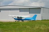 image of cessna-172  - Light Cessna propeller driven airplane parked at warehouse - JPG