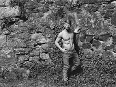 Muscular Guy On Stony Wall Backdrop poster