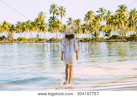 poster of Traveler Girl Walking In White Dress On A Tropical Beach. Young Girl Traveler Walking In Nature. Tra