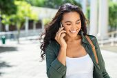 Cheerful young woman looking down on street while talking over smartphone. Smiling girl walking on s poster