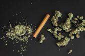 Close Up Of Addict Lighting Up Marijuana Joint With Lighter. Man Preparing And Rolling Marijuana Can poster