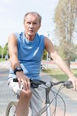 Determined senior man riding bicycle in park poster