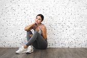 Sport Woman In Sportswear Relax After Workout Against Copy Space For Adding Text With White Wall Bac poster