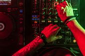 Close Up Of Dj Hands Controlling Music Table In A Night Club. poster