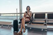 Woman Resting In Arrival Hall Waiting For A Transfer At Airport poster