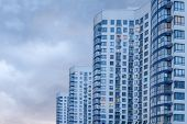 Outdoor Facilities. Apartment Building. Image Of Side View Of Big Building With Appartements At Dusk poster
