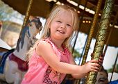 picture of carnival ride  - A little girl riding the carousel while at the carnival.