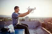 Young Technician Flying Uav Drone With Remote Control On Rooftop poster