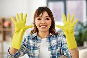 cleaning, housework and hand protection concept - asian woman in protective rubber gloves at home poster
