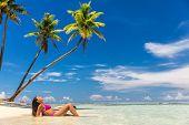 Beach vacation paradise suntan woman relaxing lying down sun tanning in tropical idyllic summer back poster