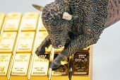 Bull Market In Gold Investment Concept, Closed Up Of Bull Figure On Gold Bar Or Ingot. poster