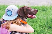The Girl Hugs A Dog Of The Breed German Shorthaired Pointer. The Child And The Dog Are Friends poster