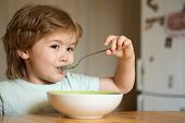 Baby Eating Food On Kitchen. Happy Child. Cute Kid Are Eating. Little Baby Are Eating. Little Boy Ha poster