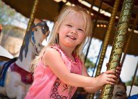 stock photo of carnival ride  - A little girl riding the carousel while at the carnival. ** Note: Slight graininess, best at smaller sizes - JPG