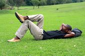 An African Man Is Lying On The Green Grass And Sleeping With His Hands Behind His Head