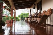 stock photo of floor covering  - A row of handmade wicker rocking chairs in a line on a covered porch with a shiny tiled floor in Costa Rica.