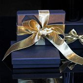 picture of close-up shot  - Close up shot of blue gift with golden bow - JPG