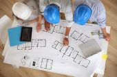 pic of blueprints  - Upper view of architects working on blueprint - JPG