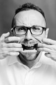foto of rabies  - Photo studio portrait of a man who opens his mouth with his hands - JPG