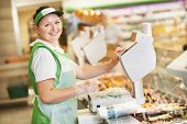stock photo of supermarket  - Smiling saleswoman assistant in supermarket working with scales balance to pregnant female customer during shopping at store - JPG