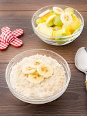 stock photo of porridge  - Oat porridge and fruits on a wooden table - JPG