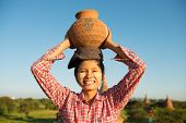 Portrait of Asian traditional female farmer carrying clay pot on head going back home, Bagan, Myanma