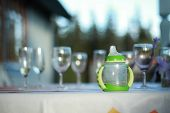 picture of muzzy  - baby bottle outdoor among some adult glasses - JPG
