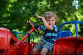 Portrait Of Little Blond Boy In Tractor In Summer