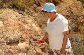 foto of paleontologist  - Senior woman geologist tap a rock formation with a hammer - JPG