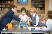 Four little children in business dress playing with toys on the table in the business center, one gi