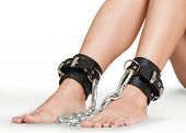 stock photo of sadomasochism  - Legs Chained in Leather Bracelets on White Background - JPG