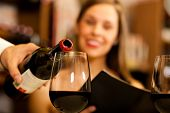 pic of waiter  - Waiter pouring red wine to a woman - JPG