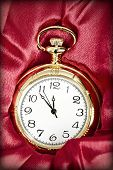 Old styled gold pocket watch on scarlet silk