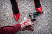 image of dominant woman  - Man is dominated by a woman with red shoes the shoe tread gun arm bloodied on the asphalt - JPG
