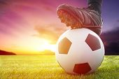 stock photo of football  - Football or soccer ball at the kickoff of a game with sunset - JPG