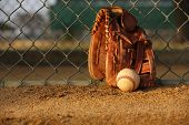 Baseball and Glove against the Field Fence