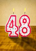 Burning birthday candles number 48 on a wooden background