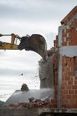 foto of backhoe  - Bucket of a backhoe or mechanical digger against the skyline demolishing the wall of a brick building with flying masonry and debris - JPG