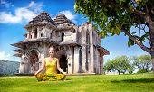 stock photo of karnataka  - Woman doing yoga near Lotus Mahal in royal center at blue sky in Hampi Karnataka India - JPG