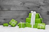 stock photo of christmas greetings  - Green Christmas presents with snow on grey wooden background for a greeting card or coupon voucher - JPG