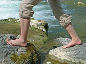 stock photo of wet feet  - Mountain creek and girls feet doing kneippism for hardening herself - JPG