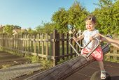 stock photo of seesaw  - Adorable little baby girl playing over a seesaw swing on the park - JPG