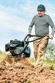 stock photo of plowed field  - Farmer plowing the field - JPG