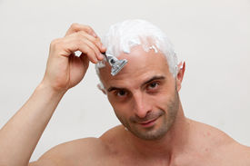 stock photo of shaved head  - Young man shaving his head with razor blade - JPG