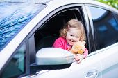 foto of teddy  - Cute laughing curly toddler girl playing with toy teddy bear sitting in a silver color modern family car on front seat watching out a window in a side mirror enjoying weekend vacation ride after rain - JPG