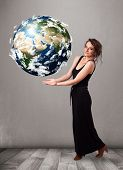 image of cartographer  - Pretty young girl holding 3d planet earth - JPG