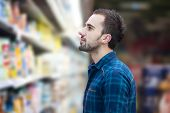 foto of grocery store  - Handsome Young Man Shopping For Fruits And Vegetables In Produce Department Of A Grocery Store  - JPG