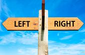foto of opposites  - Wooden signpost with two opposite arrows over clear blue sky Left versus Right messages Choice conceptual image - JPG
