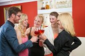 stock photo of mans-best-friend  - Group of friends a man and four women celebrating with rose wine raise their glasses in a toast of congratulations and best wishes as they stand chatting in a restaurant - JPG