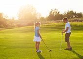 picture of pretty-boy  - Boy and little girl at a golf field holding golf clubs - JPG